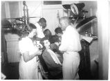 Dr. Clarence Holmes and Assistant work on Patient