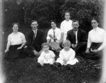 Group of children an adult seated on a lawn