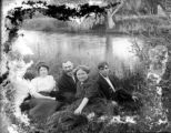 Five people sitting by the river