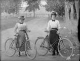 Two women on a country road with their bicycles