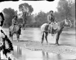 Two men on horseback on a sand bar in the South Platte