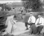 Two men seated by dam