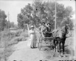 Transportation - two men riding in carriage, woman standing beside it