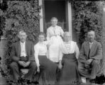 Two men and three women all older posing on a porch