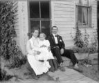 Family seated on front stoop of residence