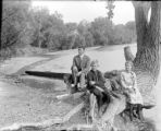Man boy & girl seated on tree roots by the river