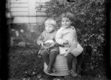 Two children sitting on tub outside