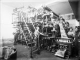 Men at work on printing presses as paper is printed