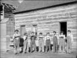 Agriculture - ranching - women in work clothes eating watermelon in front of log house