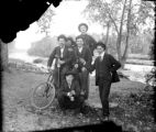 Group of men one with bicycle along stream