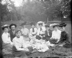 Recreation picnic group sitting on blanket in a park