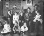 Family (man, woman, 7 children) seated for photograph - interior