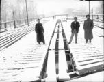 Three men standing on the Alameda Avenue bridge during construction