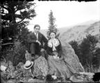 Couple seated together on rock mountain background