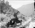 Harry Rhoads on mountain road waving from a 1915 Maxwell