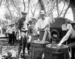 Three men stirring a barrel