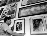 Mike Lucero - employee at Centro Cultural hangs paintings for centro art exhibit