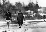 Sioux women carry groceries home in sack note contrast in skirt lengths.