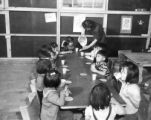 Milk and graham crackers being served to nursery school children in a block recreation hall