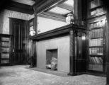 Massive fireplace in library stretches across almost one end of room