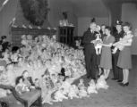 Telephone company girls give dolls to firemen for Xmas