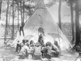 Indians playing cards in front of tent