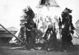 Native American men in front of teepee