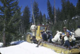 Arnold Faucus (foreground) w / film crew a one track snowcat, steered with skis from behind the...