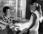 Mrs. James A. Wilson, Children's Librarian, confers with a customer