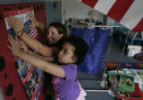Kindergarten teacher Michelle Lang (cq) gets help hanging a pledge of allegiance poster from 4th...