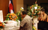 Yvonne Trujillo(cq), right, takes a picture of Deion Santistevan, 5, as he lays in his casket...