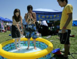 Alicia Harris, 17, left, of Aurora, and Yang Yang, 17, of Aurora, try to fill their kiddy-pool...