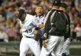 MLB Umpire Greg Gibson (#53) holds back Rockies' pitcher  Jose Mesa, left,  during the bottom of...