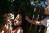 Celine Venzer, cq, 7, left, and her brother Kenny, 2, play with their chihuahua...