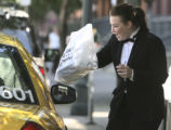 Kimberly Geherin (cq), Assistant Manager of Morton's Steakhouse, hand a box lunch to a Yellow Cab...