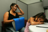 Trinity Gallegos (cq), 4, right, rests her head on a desk while her mother Arlene Gallegos (cq),...