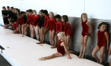 Mikayla Novacek, 7, stretches and warms up while doing the spilts on mat before she and other...
