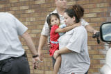 Alize Martinez, 4, left, is carried by her mother(((NAME?))) from the Fort Lupton police station...