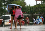 Olga Pense (cq), left, and Juliana Gomez (cq), right, protect themselves from the rain while...