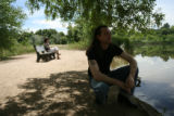 Ryan Brassell kneels next to the lake at Prospect Park as his ex-wife Beverly Brassell sits on a...