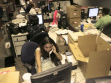 Rocky Mountain News business reporter Gargi Chakrabarty (cq) has boxes piled on her desk while...