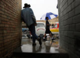 Leaning against a building in the rain, Mike Alexander(cq), left, leans against a building and...