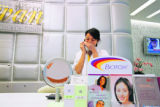 An employee of Siam Swan Cosmetic Clinic in Bangkok, talks on the phone at the salon where John...