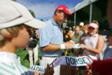 PGA Tour professional Olin Browne (center, in blue and white striped shirt) signs autographs for...