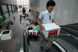 Chris Laughlin, 24 of Denver carries a box full of petitions up the escalator to the Secretary of...