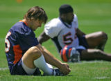 Broncos' quarterback Jake Plummer (#16) stretches out with teammate Al Wilson (#56) before...