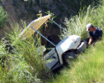 David Tice from Chapita Golf Course replaces a tire before pulling the stollen golf cart out of a...