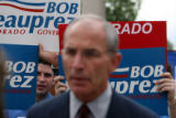 Wes Parham, cq, special assistant to Congress Bob Beauprez, peep around a sign he holds up,...