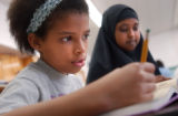 (Denver, Colo., May 6, 2004)  Hajar El Asri, 11, left and Fartun Wako, 11, right, work on homework...