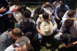 (Jefferson County, CO., June 22, 2004)Bull riders bow their heads in prayer before competing...
